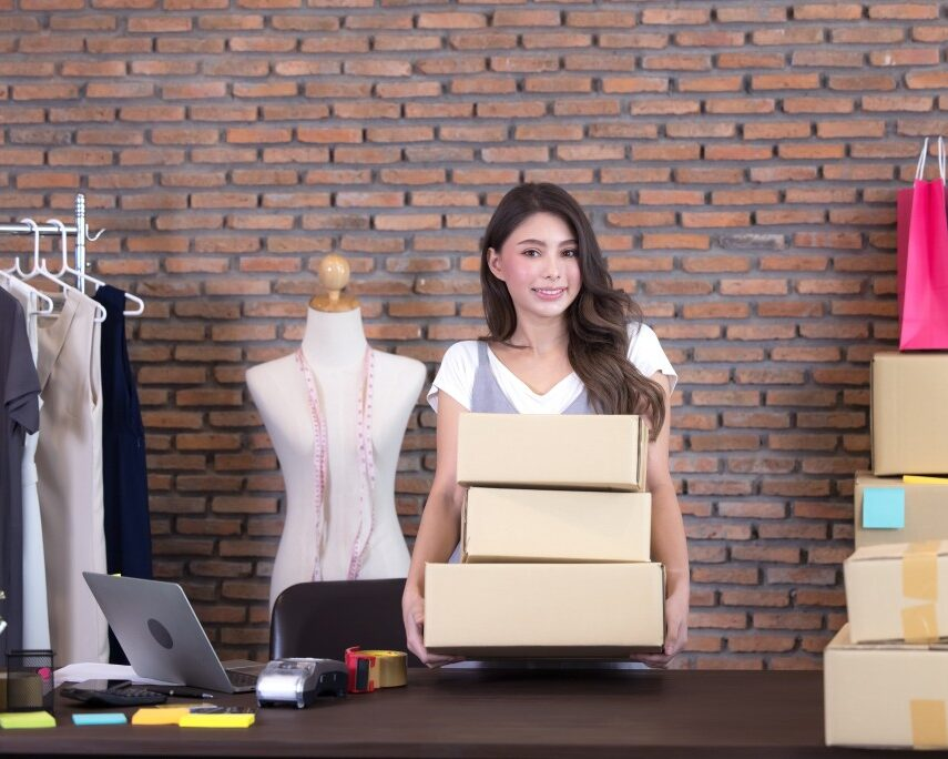 CollectCo beautiful asian woman standing among several boxes and checking parcels working in the house office t20 aaRy0w